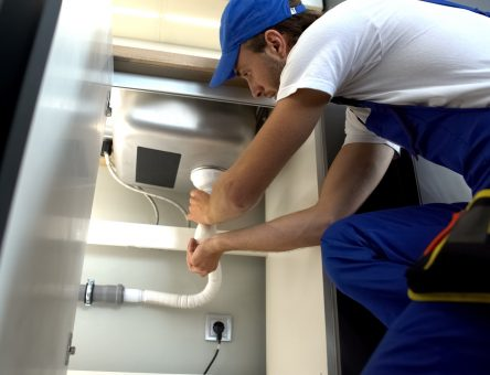 plumber fixing sink line - Tom's Plumbing and Drain Service, LLC