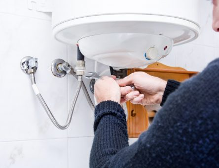 a plumber holding a spanner tool while installing a water heater - toms plumber